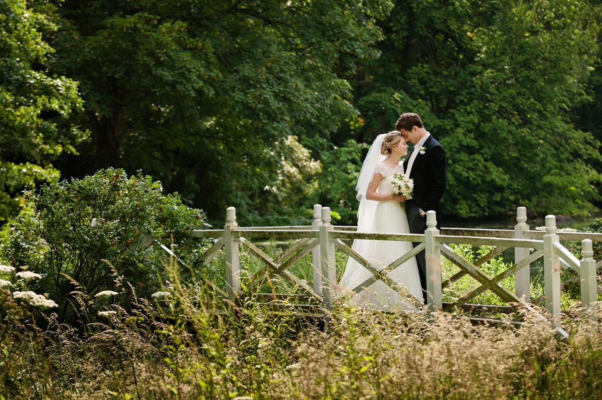 Bride and groom on white painted bridge at Exton Park, Rutland