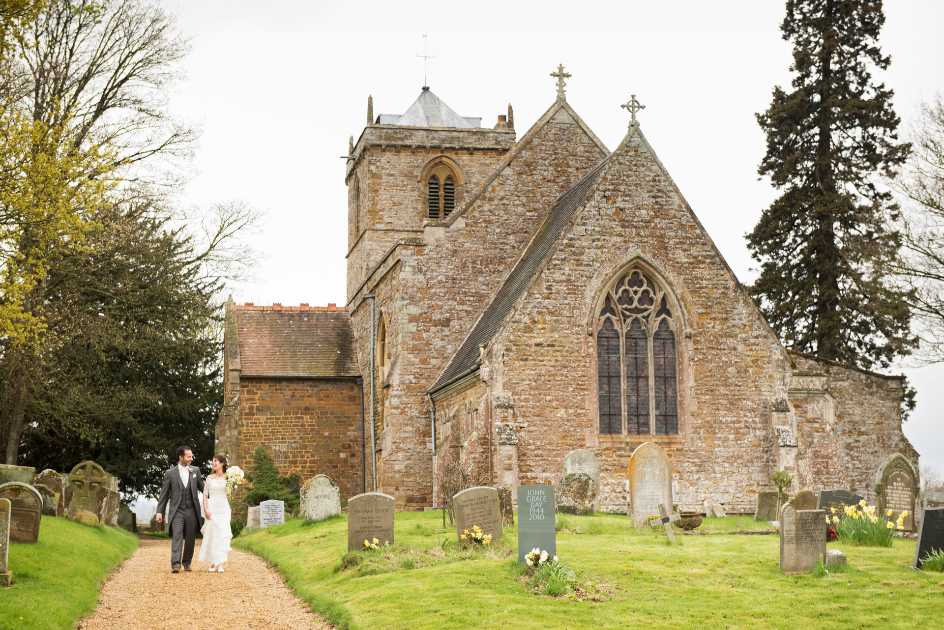 Bride & Groom walking down the path at Dodford church