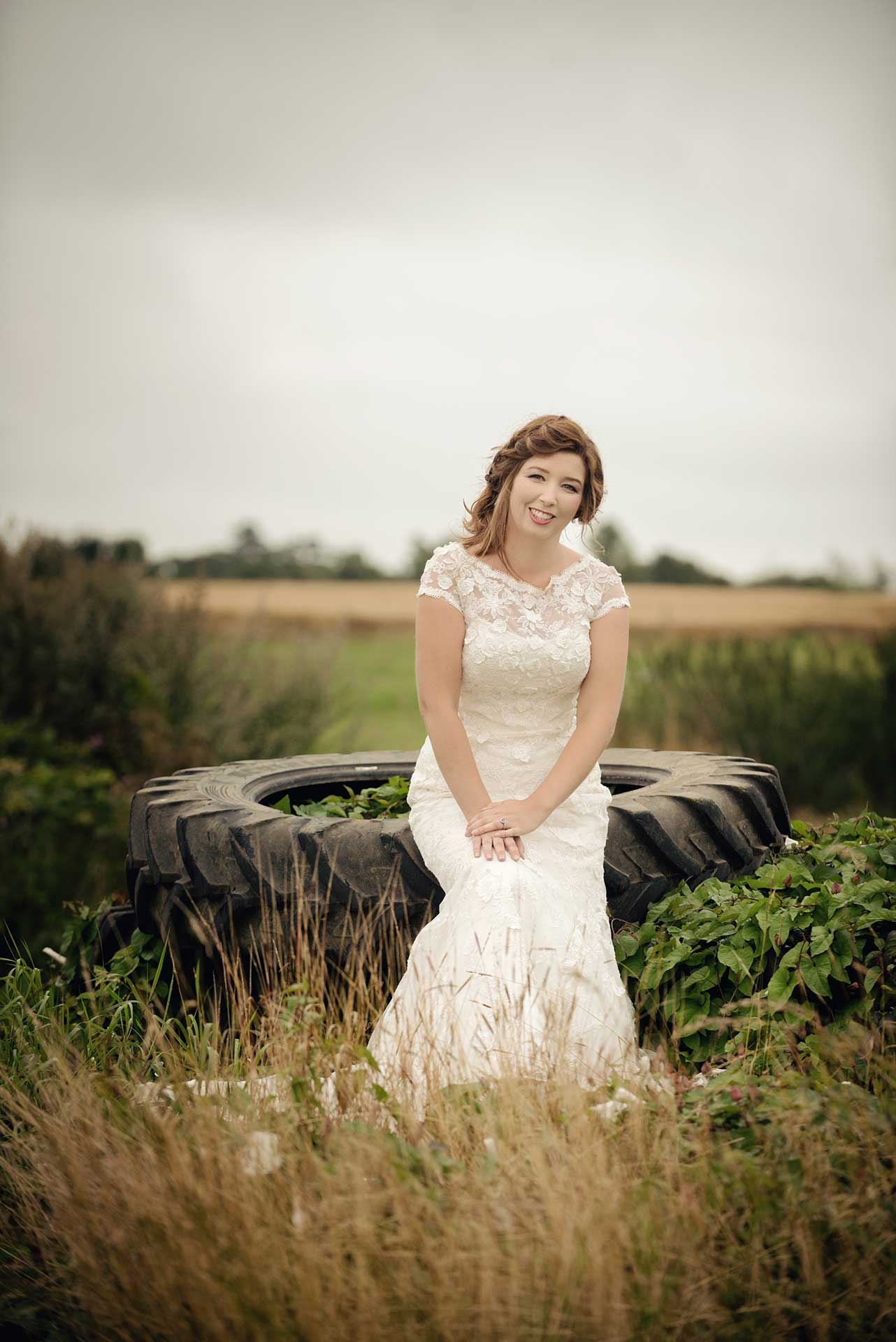 Bridal fashion shoot on a farm with an old tyre