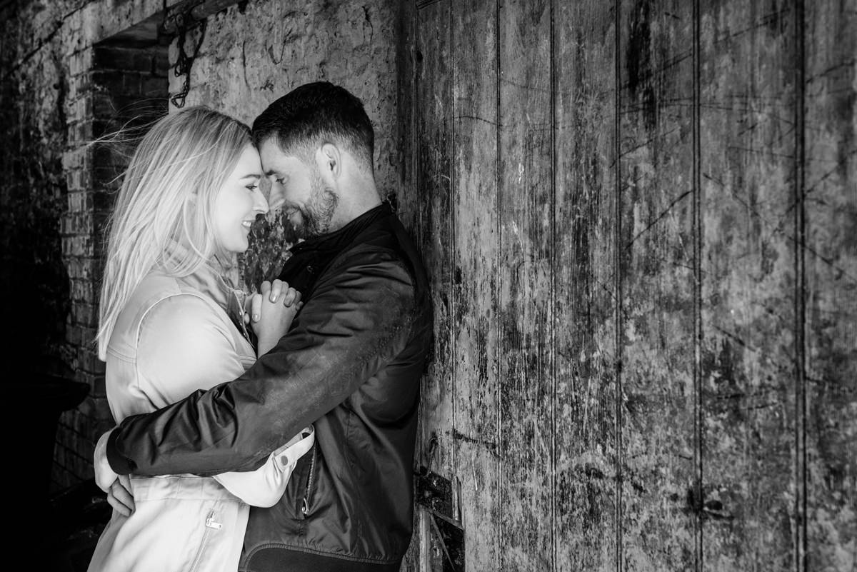 Engaged couple in front of an old wooden door