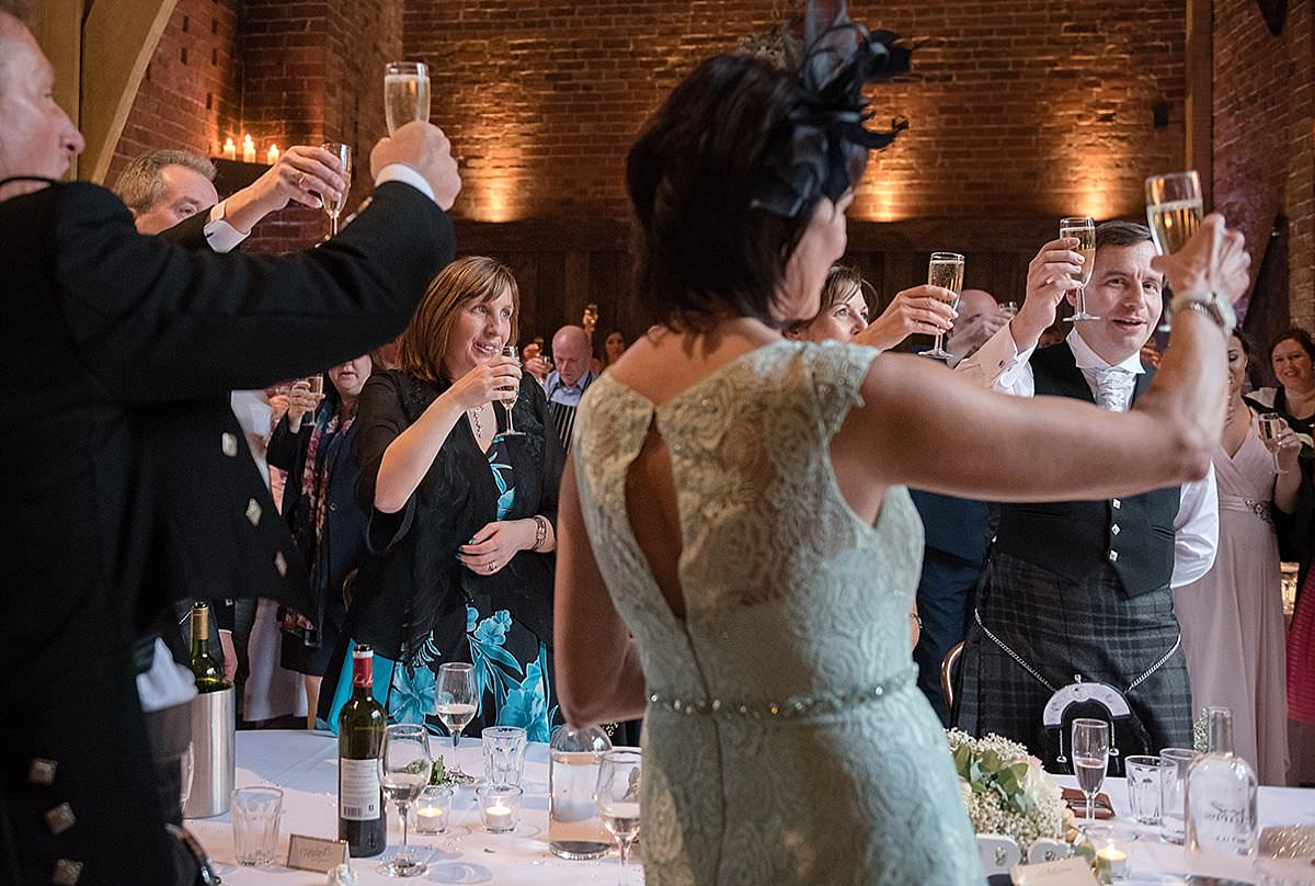 Guests making a toast after a wedding speech at Shustoke Farm Barns in Coleshill