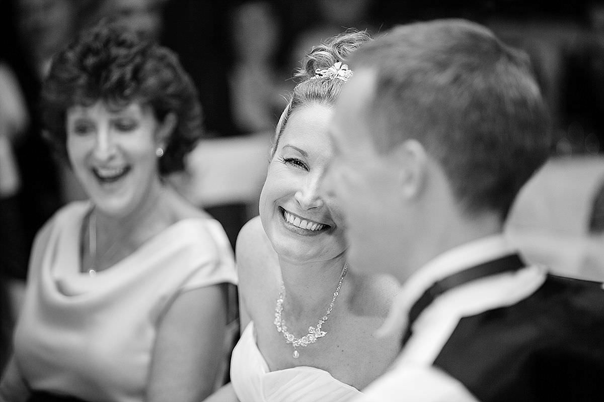 A bride smiling at the Groom during the speeches at Rushton Hall in Northants