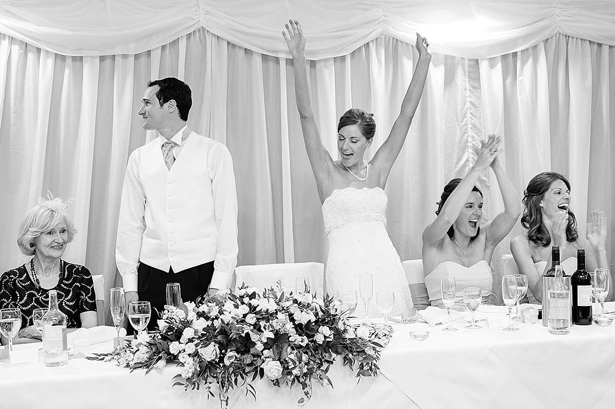 Bride cheering during the speeches at Rushton Hall in Northants