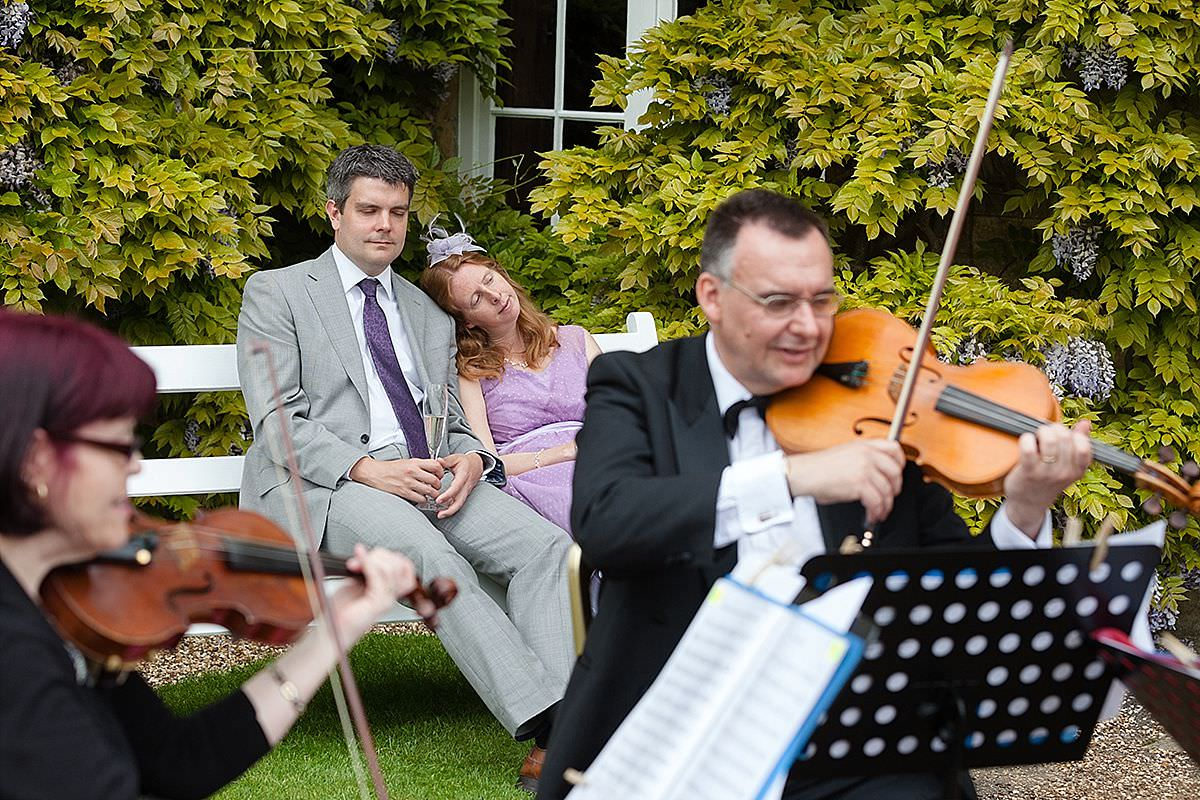 Wedding guests fallen asleep while the string quartet play at Boughton House in Northamptonshire