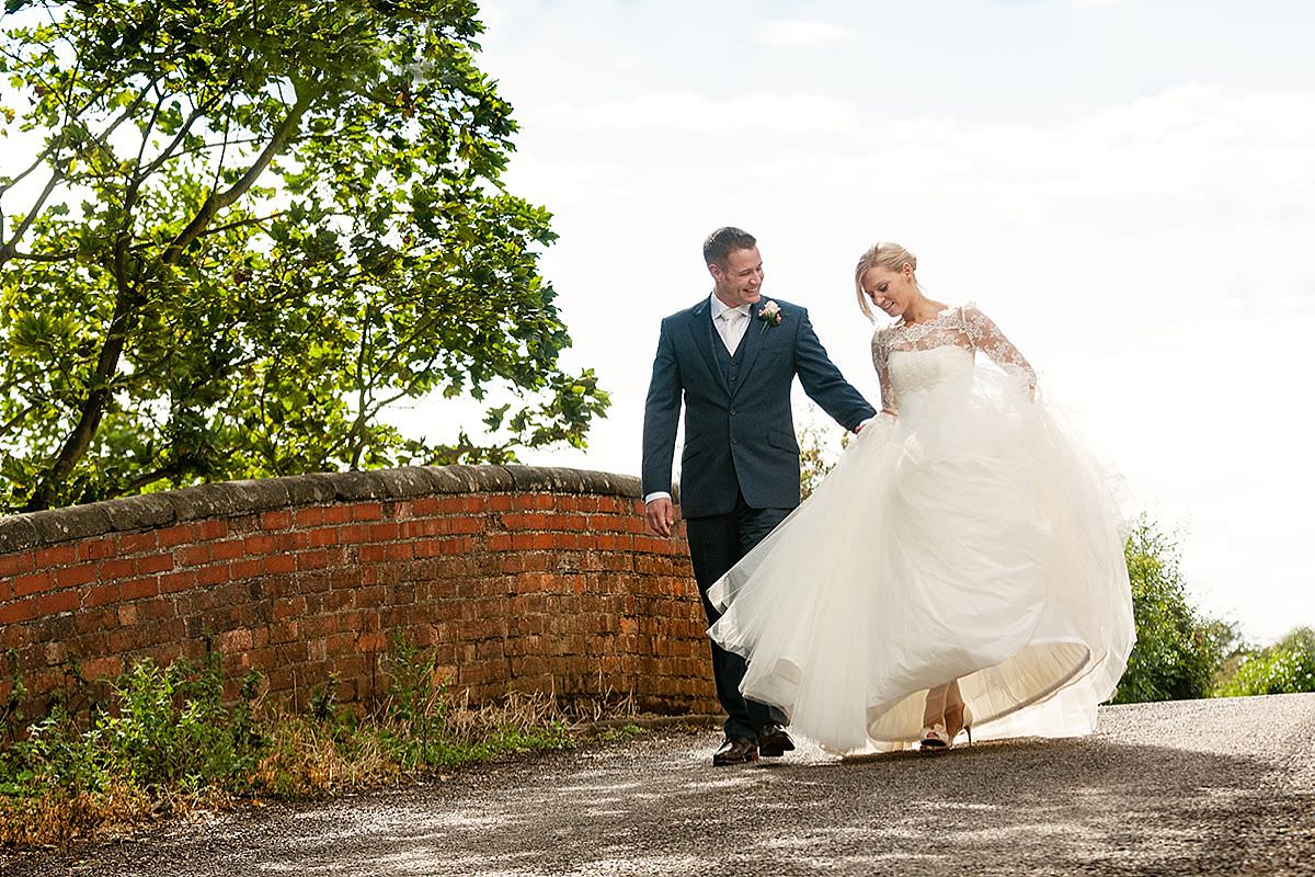 A bride & groom walking in the lane at Dodmoor House in Northants