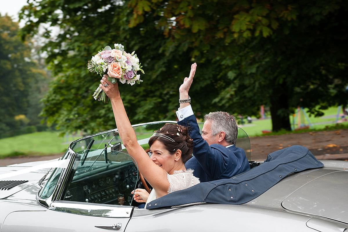 Bride & Groom waving as they leave Abington Park church in Northampton
