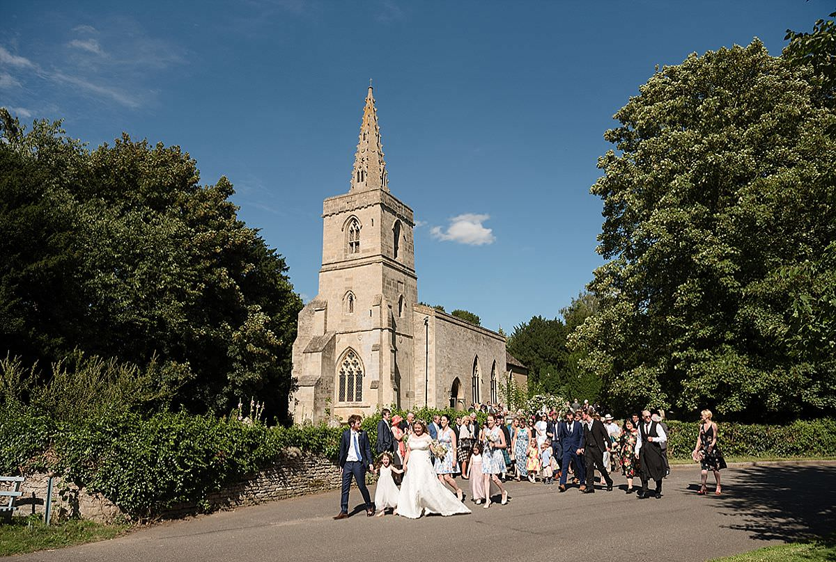 Bride & Groom walking from the church to their reception in Southwick, Oundle