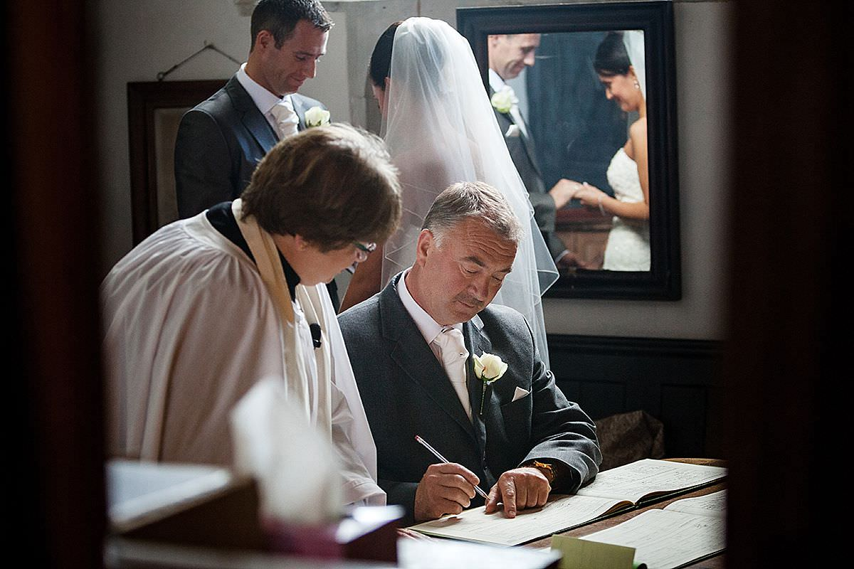 Father of the bride signing the register at Potton church in Bedfordshire