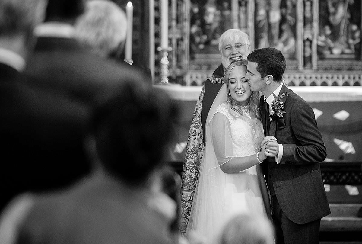 Bride & groom's first kiss at Calne church near Marlborough in Wiltshire