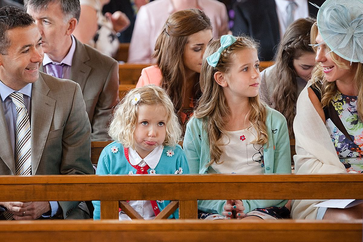 Little girl pulling a funny face while waiting for the wedding ceremony in Northampton