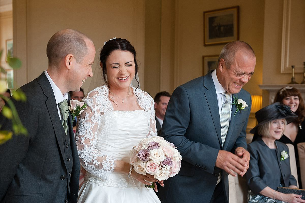 Bride & her father laughing during the ceremony at Rushton Hall in Northants