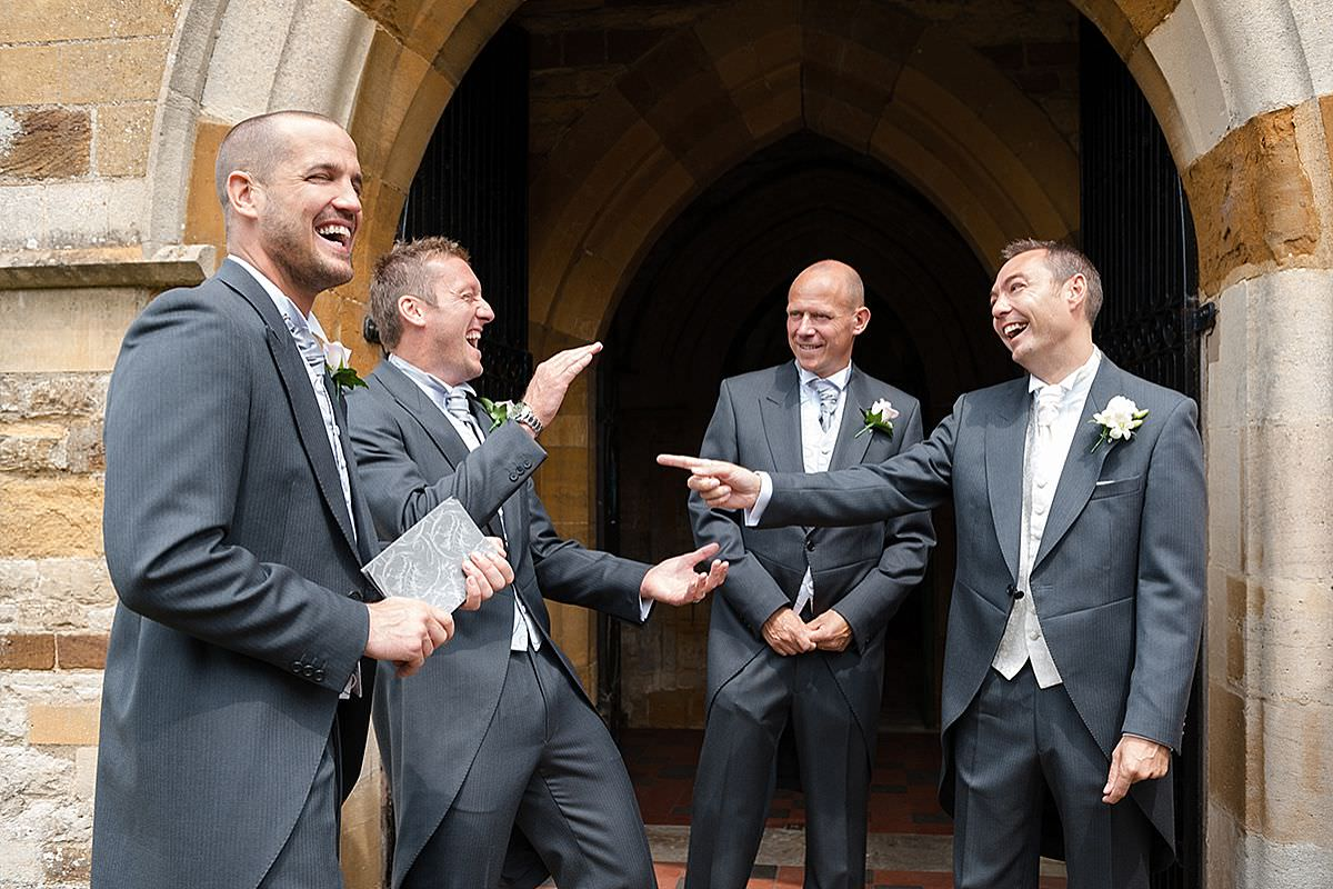 Groomsmen laughing outside the church in Wootton, Northampton