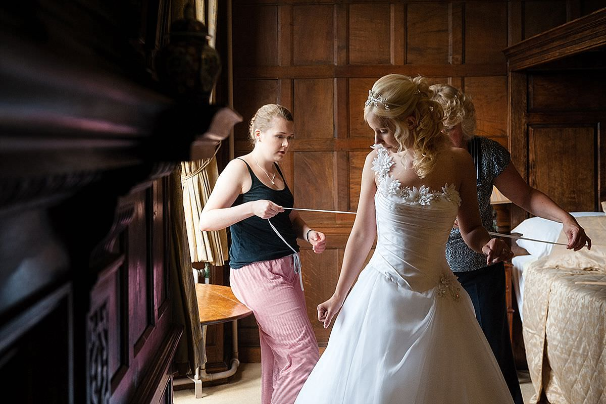 Bride getting into her wedding dress at Rushton Hall in Northants