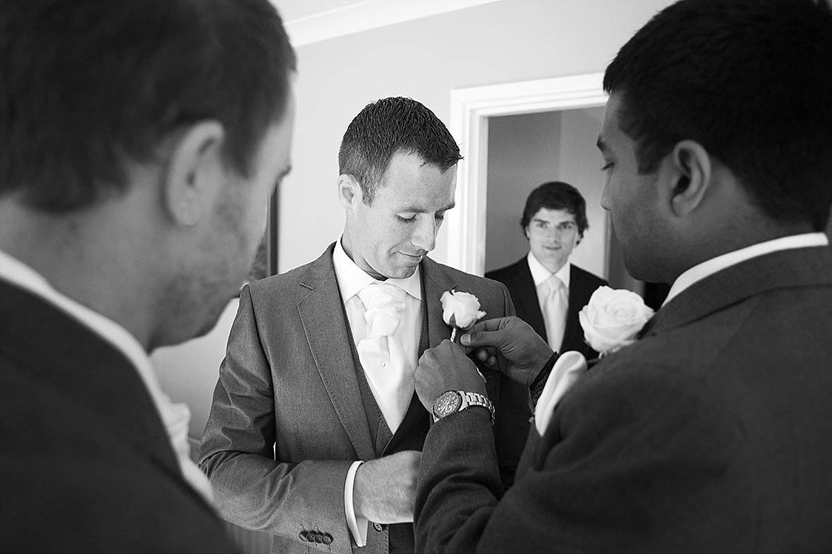 Groomsmen putting their buttonholes on in Potton, Bedfordshire