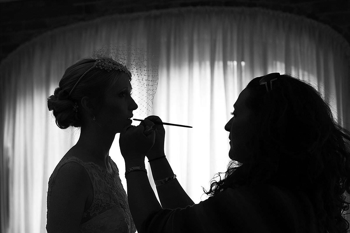 MakeUp artist putting the Bride's lipstick on at Dodmoor House in Northants