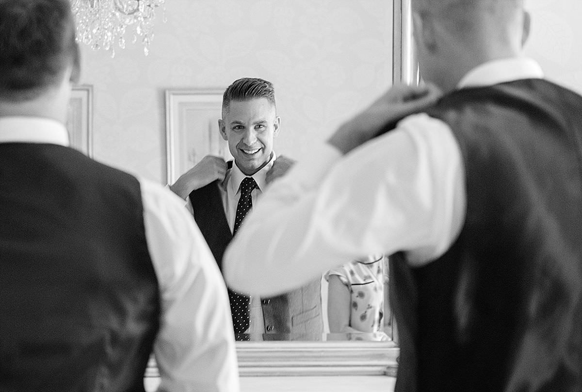 Groom putting his waistcoat on at Rushton Hall in Northants