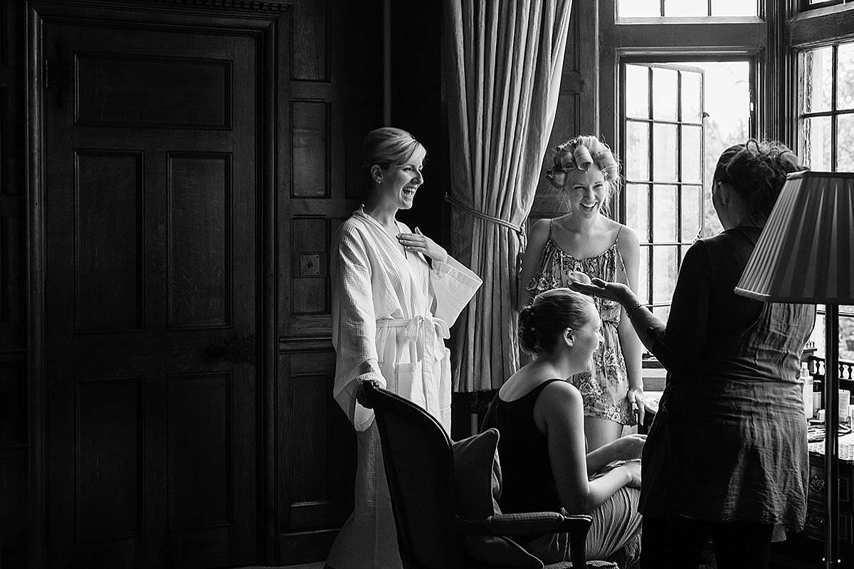 Bride laughing with her bridesmaids at Rushton Hall in Northants
