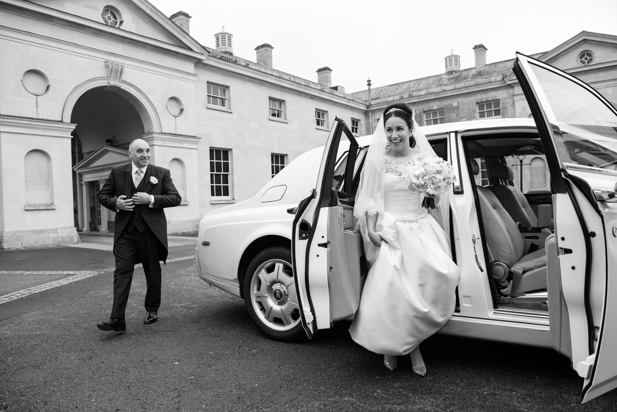 Bride getting out of wedding car at The Sculpture Gallery, Woburn Abbey