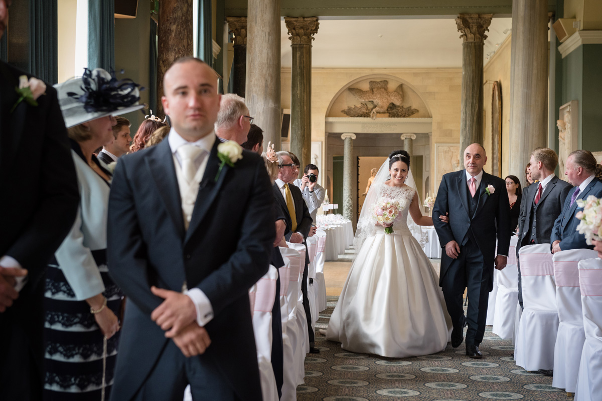 Bride walking down the aisle at The Sculpture Gallery, Woburn Abbey