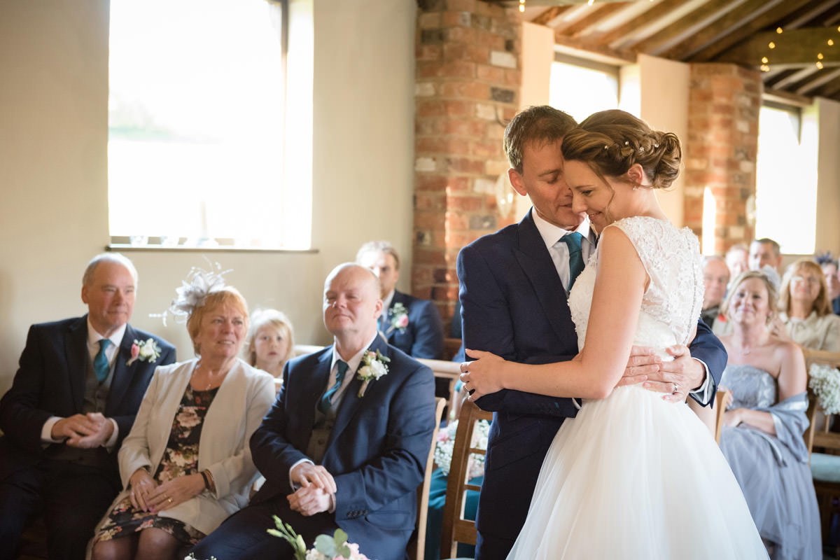 Groom whispering in Bride's ear during wedding ceremony at Dodmoor House