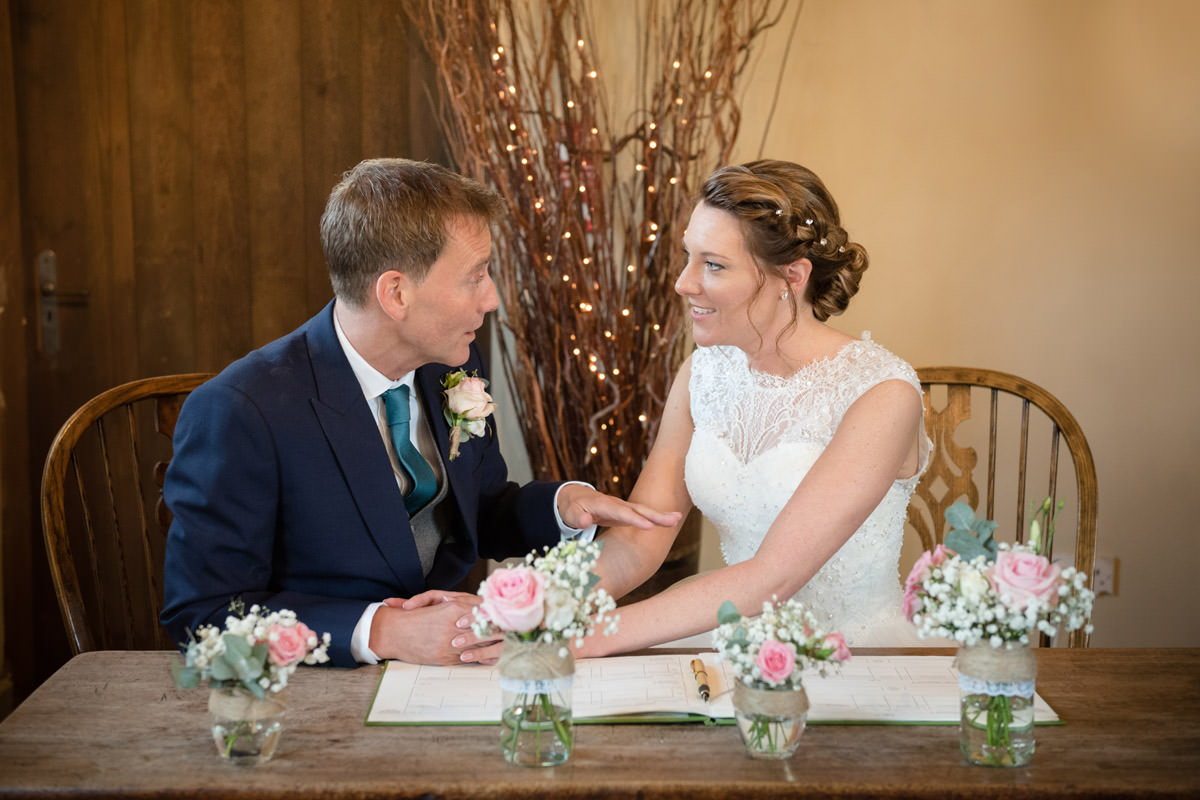 Bride & Groom chatting during the signing of the register at Dodmoor House