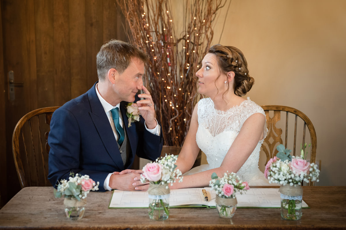 Bride & Groom talking during the signing of the register at Dodmoor House
