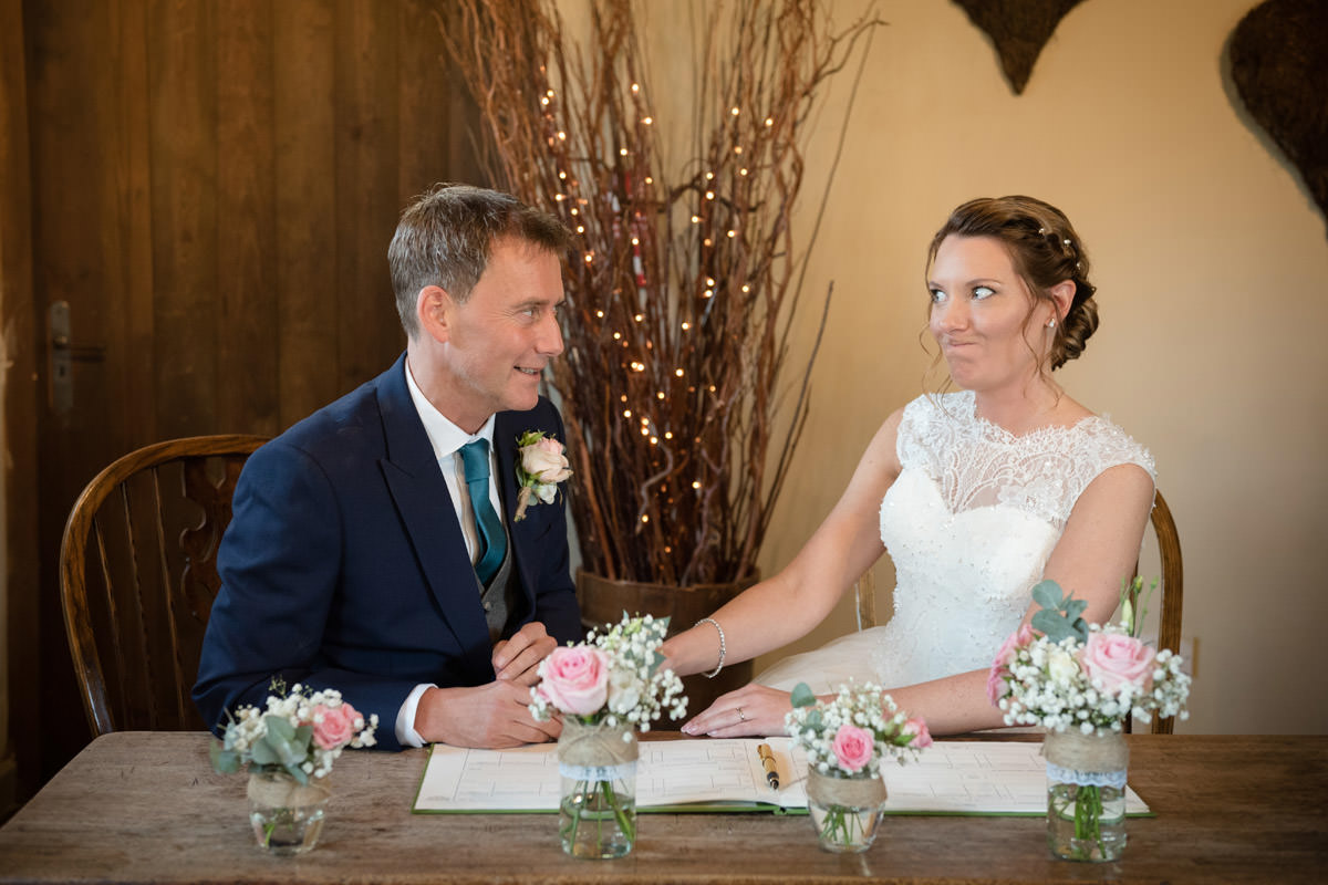 Bride pulling a face at the Groom during the signing of the register at Dodmoor House