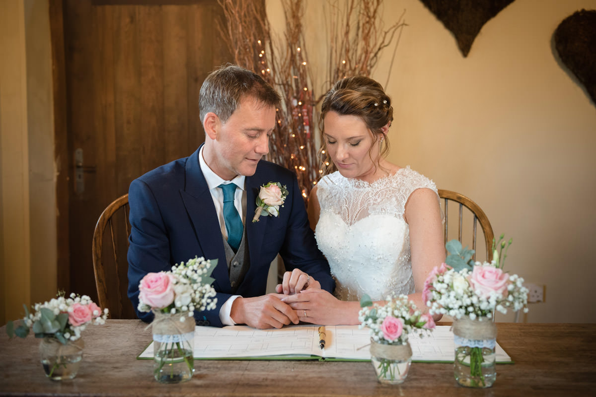 Bride & Groom looking at wedding rings during the signing of the register at Dodmoor House