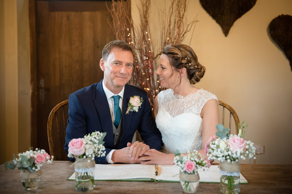 Groom smiling during the signing of the register at Dodmoor House