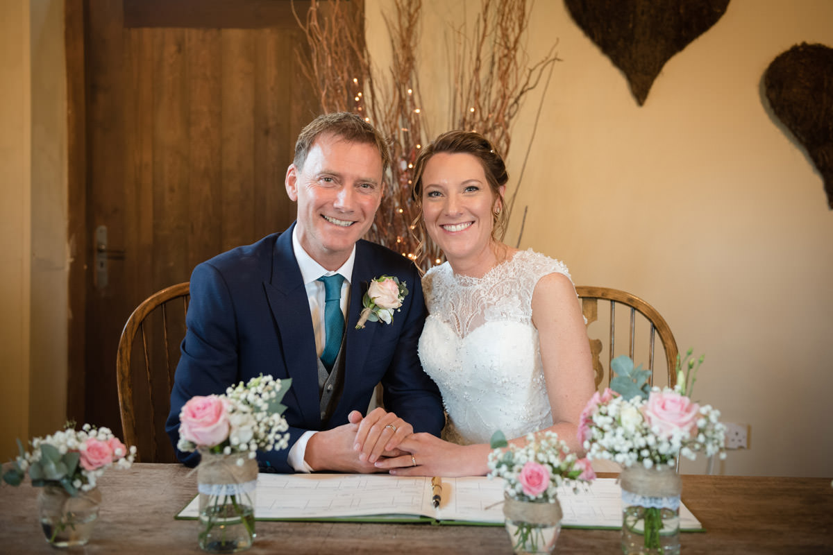 Bride & Groom smiling during the signing of the register at Dodmoor House