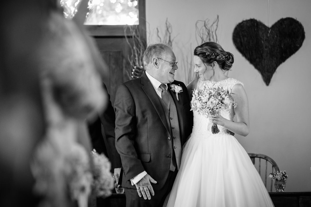 Bride & her Dad smiling at each other at the end of the ceremony at Dodmoor House