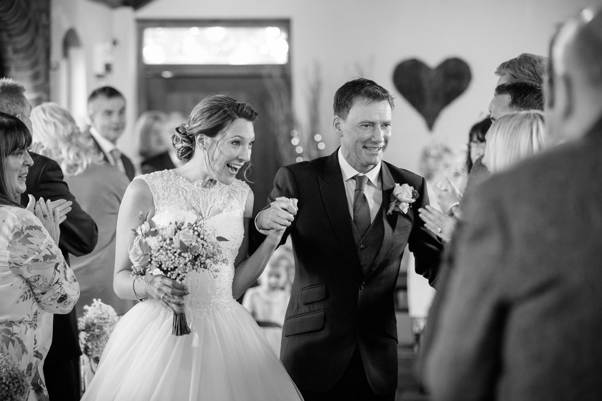 Bride & Groom chatting to guests as they walk down the aisle at Dodmoor House