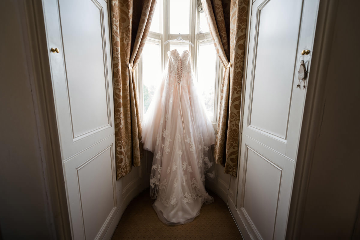 Bride's dress hanging in the bridal suite at Stoke Rochford Hall, Grantham