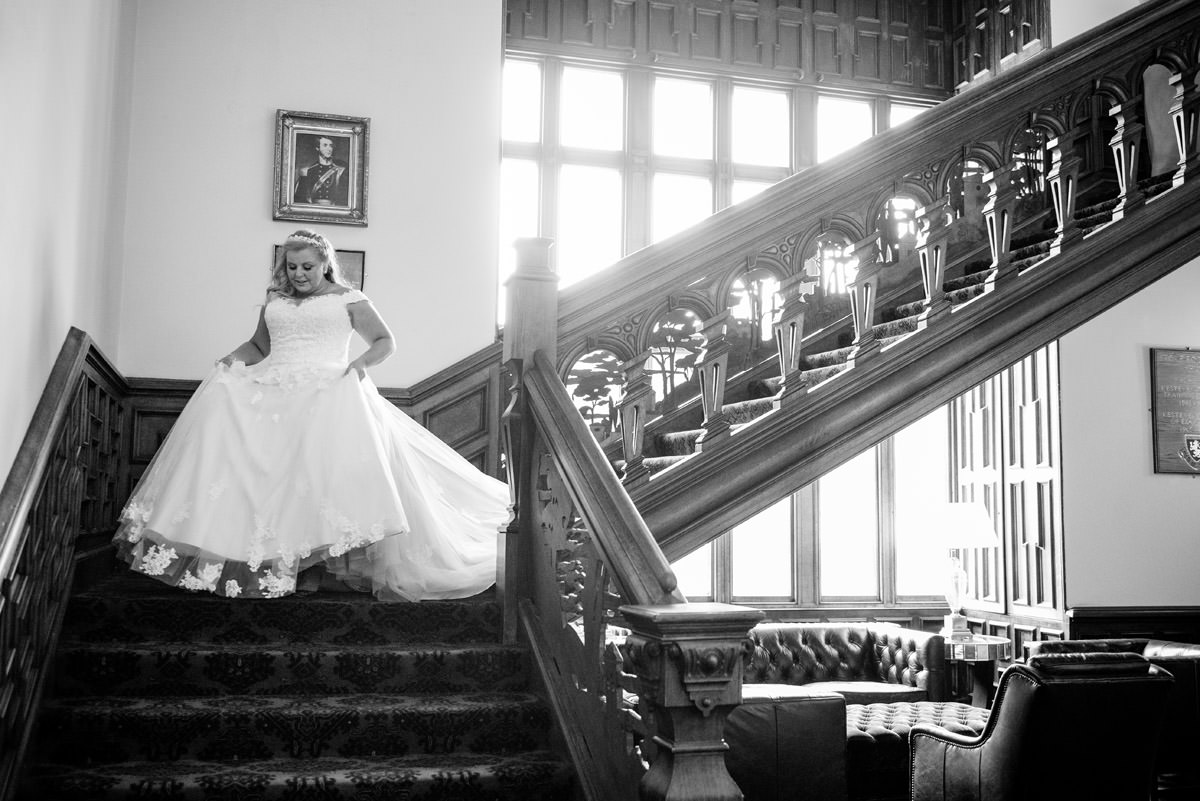 Bride coming down the stairs at Stoke Rochford Hall, Grantham