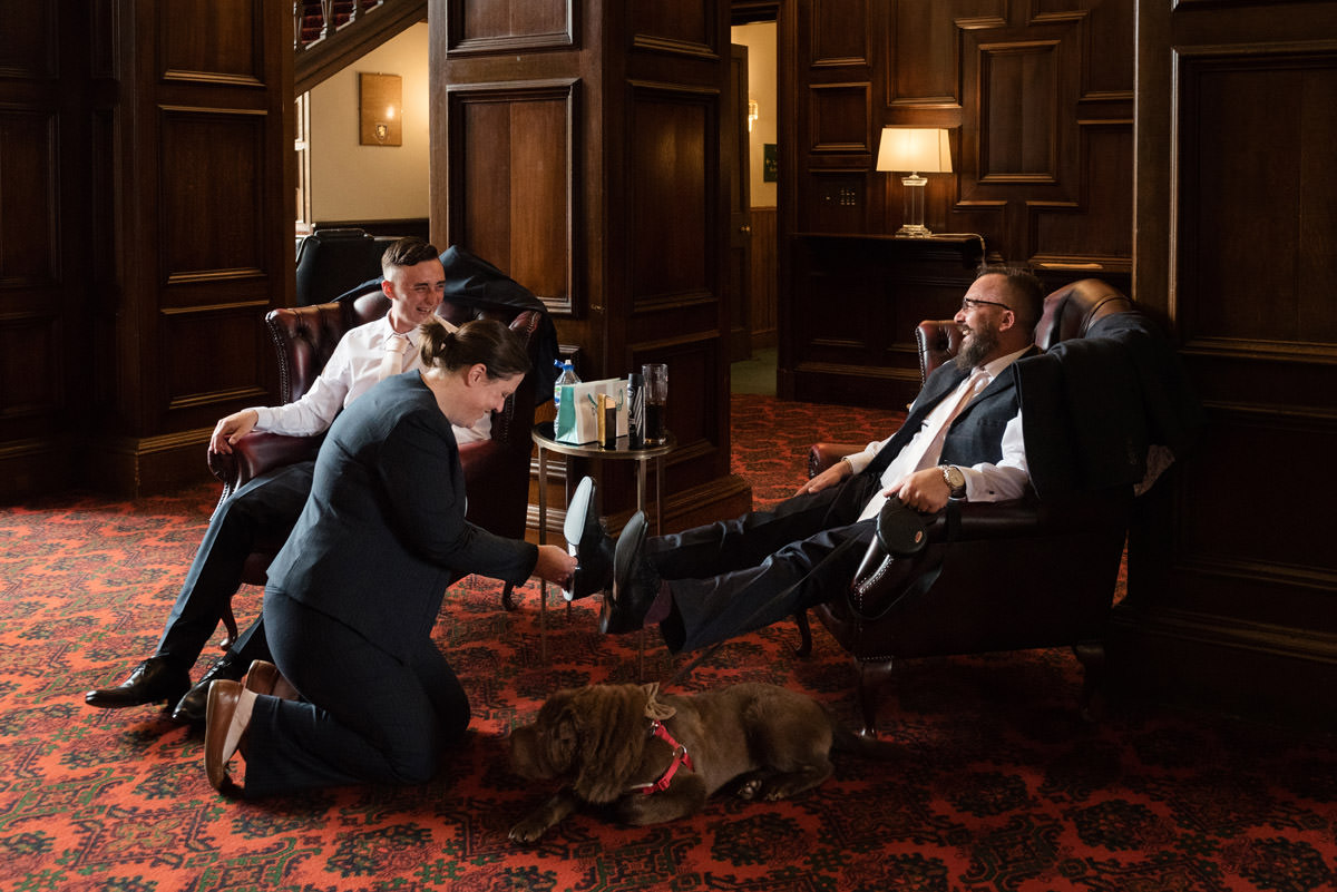Groomsmen taking labels off the bottom of their shoes at Stoke Rochford Hall, Grantham