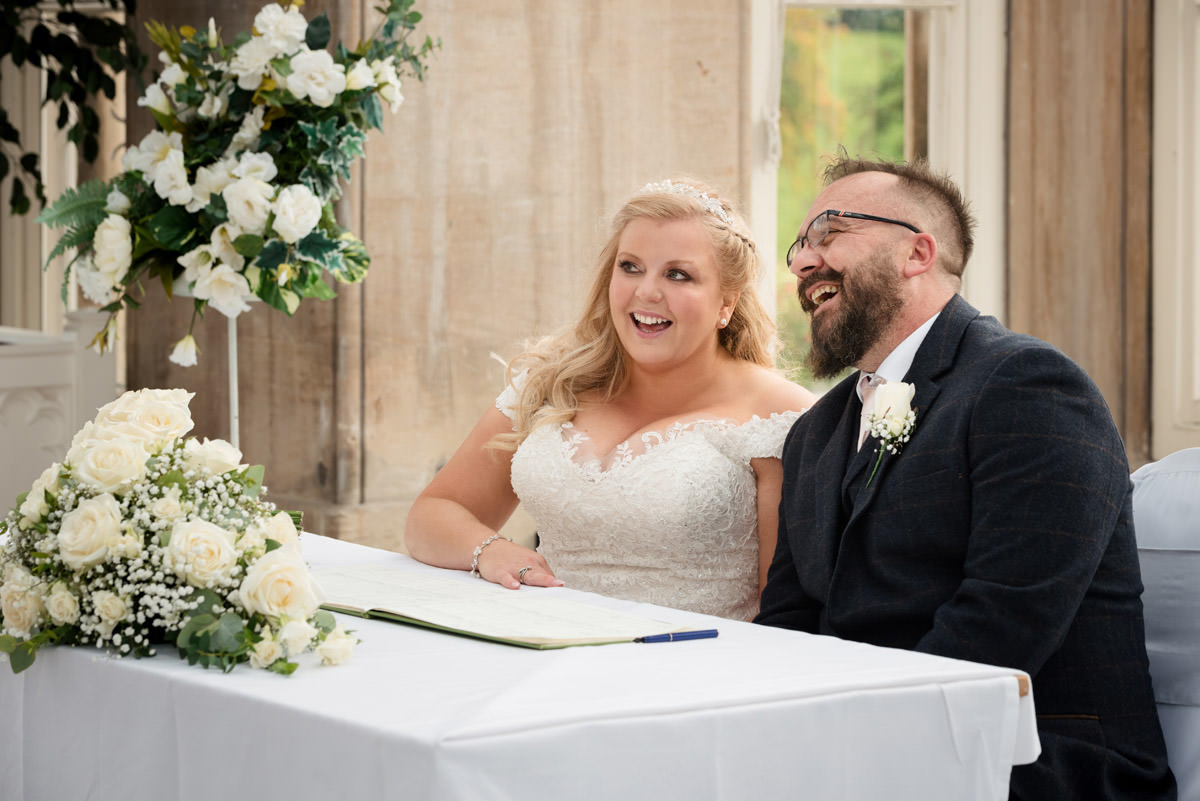Bride & Groom signing the register at Stoke Rochford Hall, Grantham