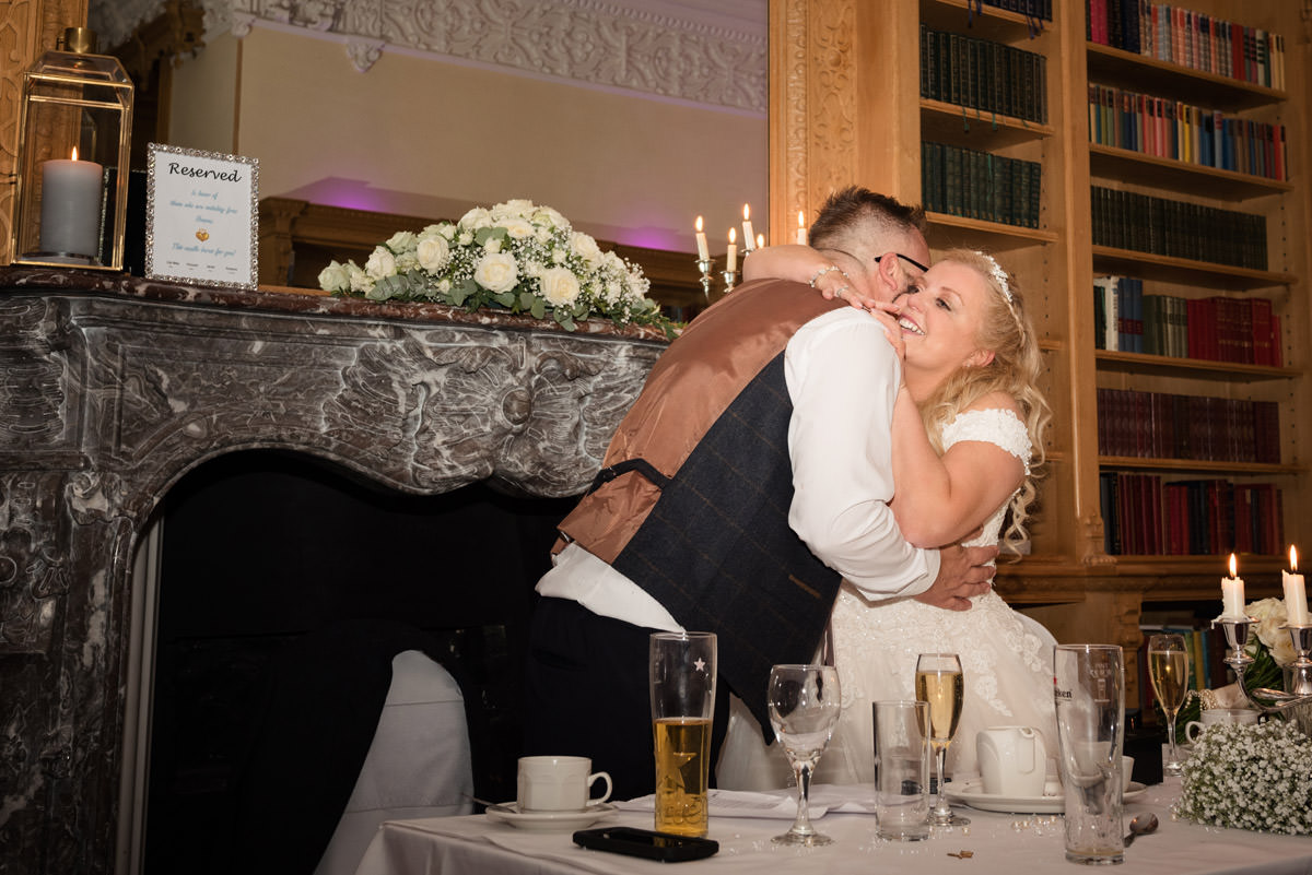 Bride & Groom hugging during the speeches at Stoke Rochford Hall, Grantham
