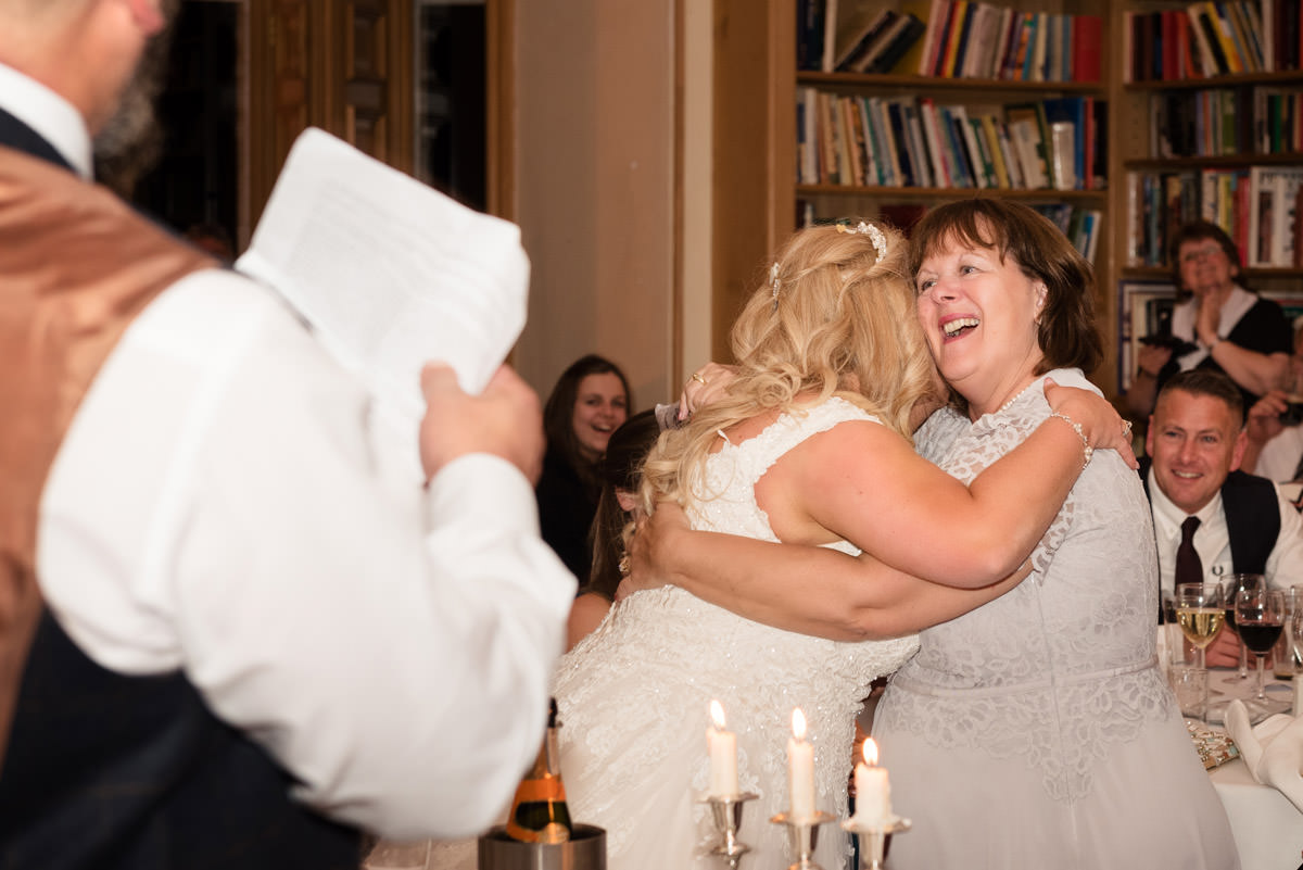 Bride & guest hugging during the speeches at Stoke Rochford Hall, Grantham