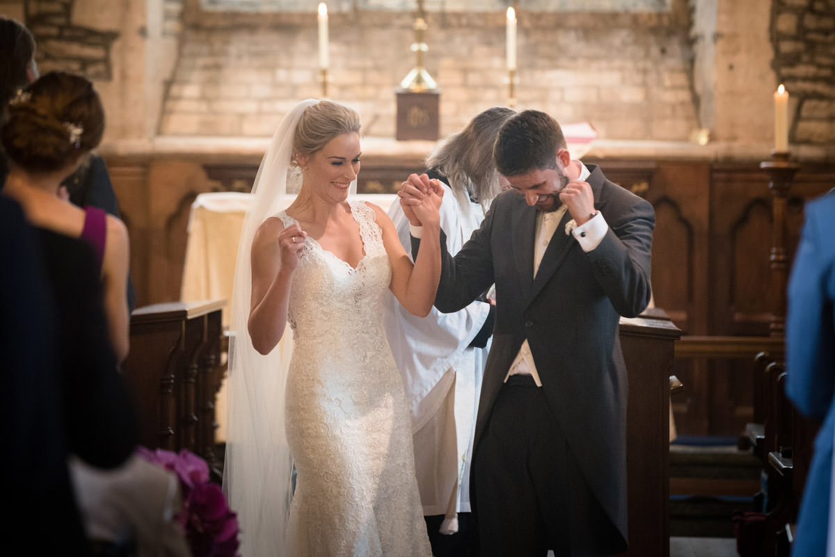 Bride & groom pumping their fists at Woodnewton church in Peterborough