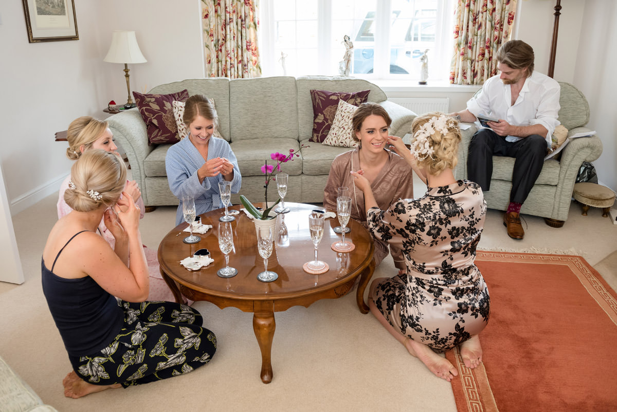 Bride giving her bridesmaids earrings as a gift on the wedding morning
