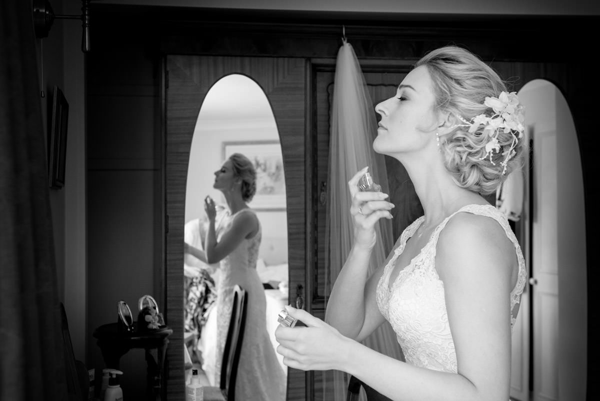 Bride spraying perfume as she gets ready
