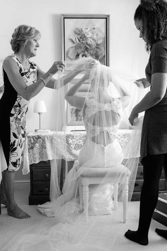Bride's Mum & hairdresser helping the bride with her veil