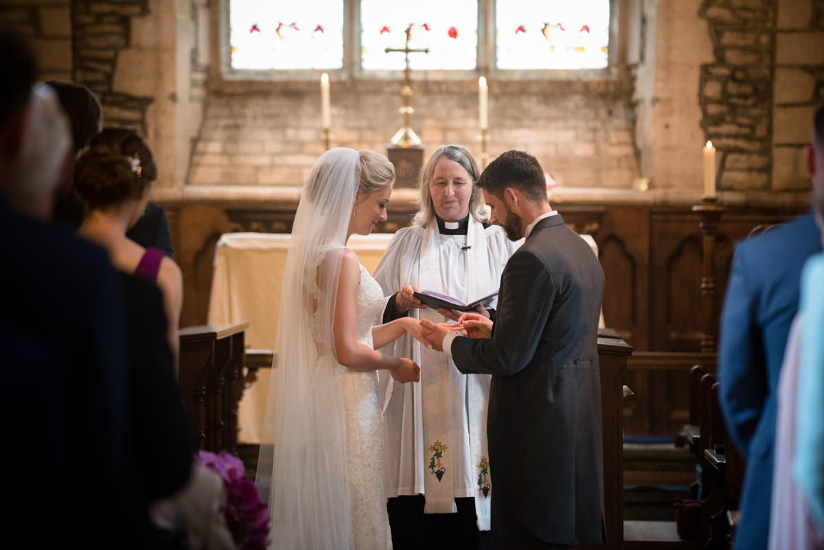 Bride & Groom exchanging wedding rings at Woodnewton Church near Peterborough