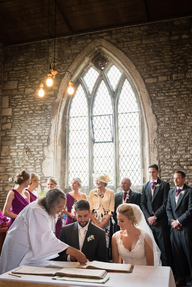 Bride & Groom signing the marriage register at Woodnewton Church near Peterborough