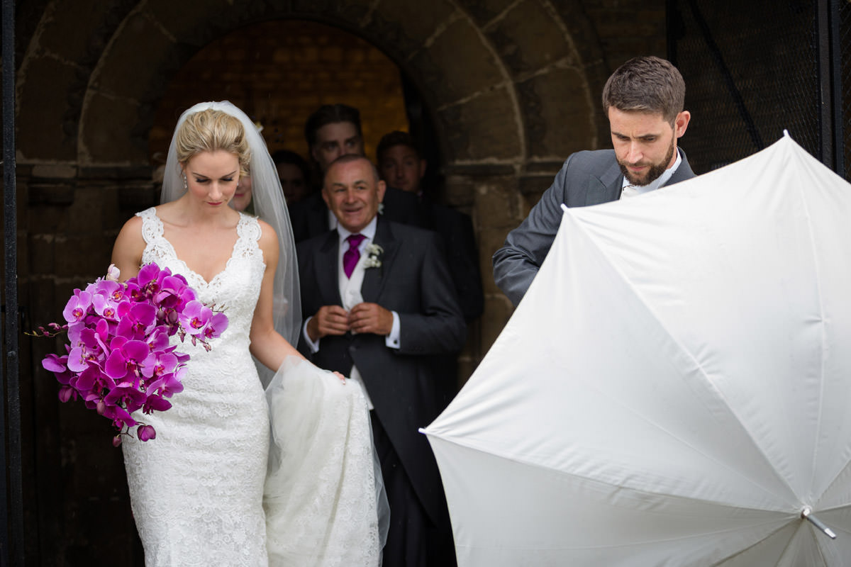 Bride & Groom leaving Woodnewton Church under umbrellas