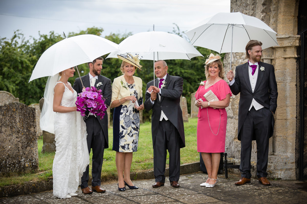 Bride, Groom & guests standing under umbrellas at Woodnewton Church near Peterborough