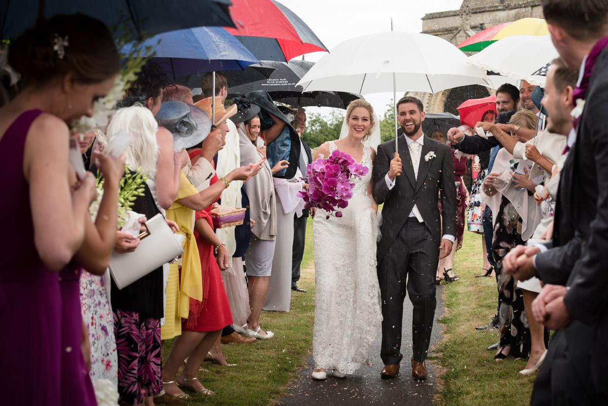 Bride & Groom under umbrellas as they leave Woodnewton Church near Peterborough
