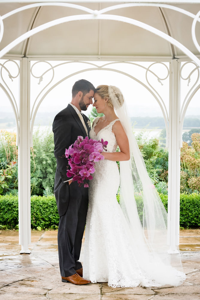 Bride & Groom sheltering under a pergola for photos at Barnsdale Hall Hotel on Rutland Water