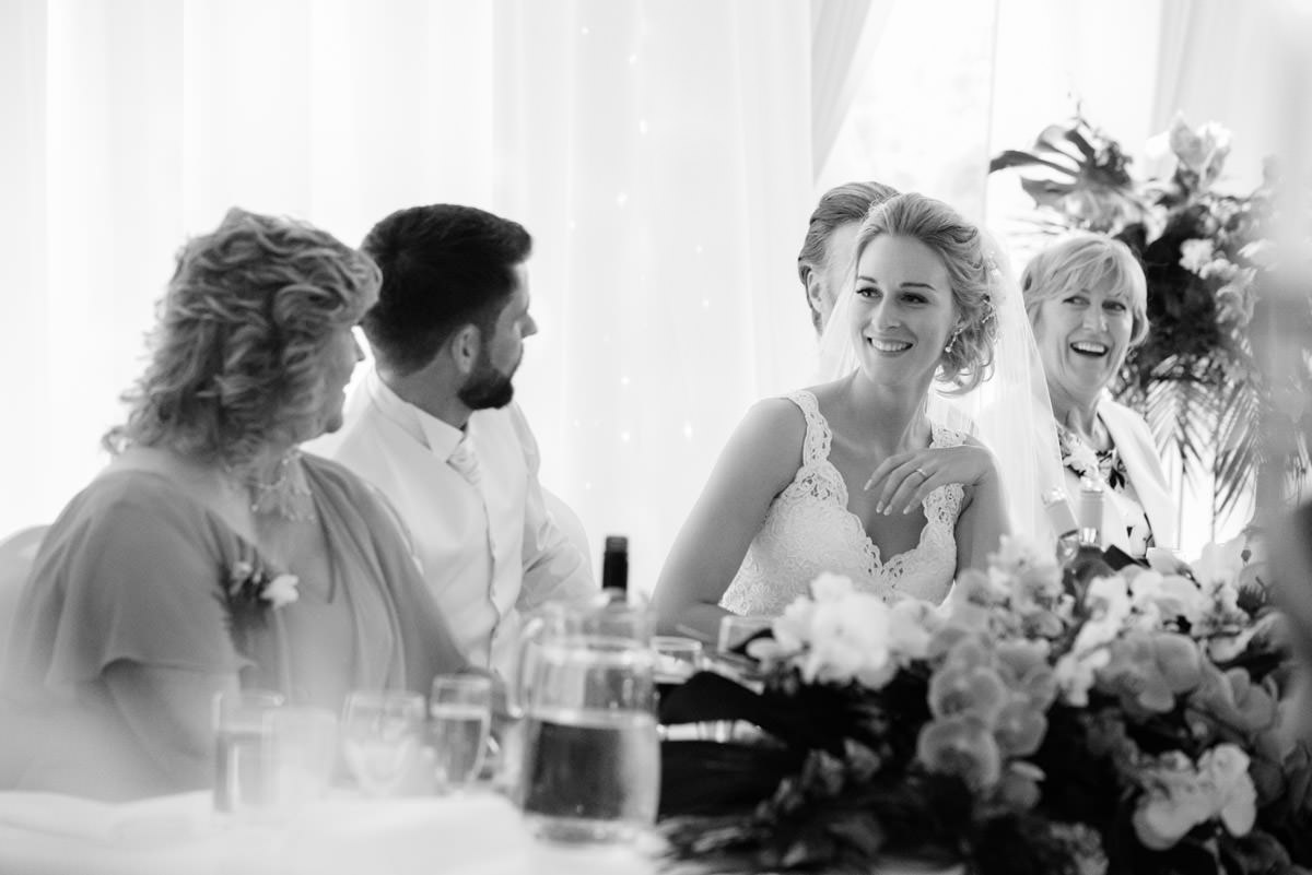 Bride laughing during the speeches at Barnsdale Hall Hotel on Rutland Water
