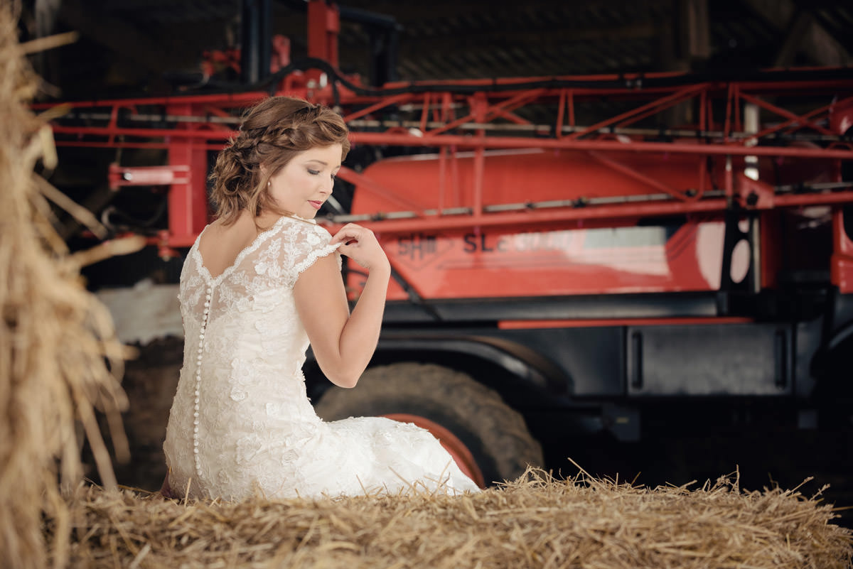 Bride sitting on a haybale